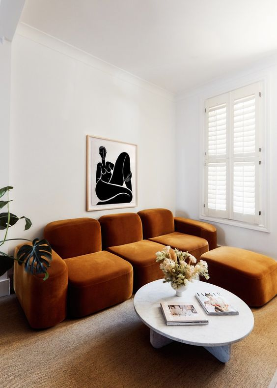 a whimsical living room with a quirky rust-colored sofa and an ottoman, a round table and a bold artwork
