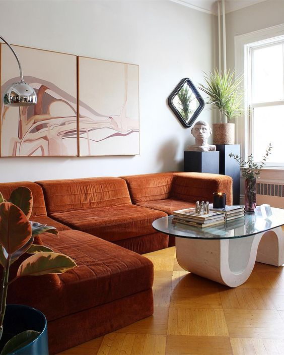 a whimsical space with a rust-colroed sectional, a quirky table, potted plants and a lovely artwork is wow