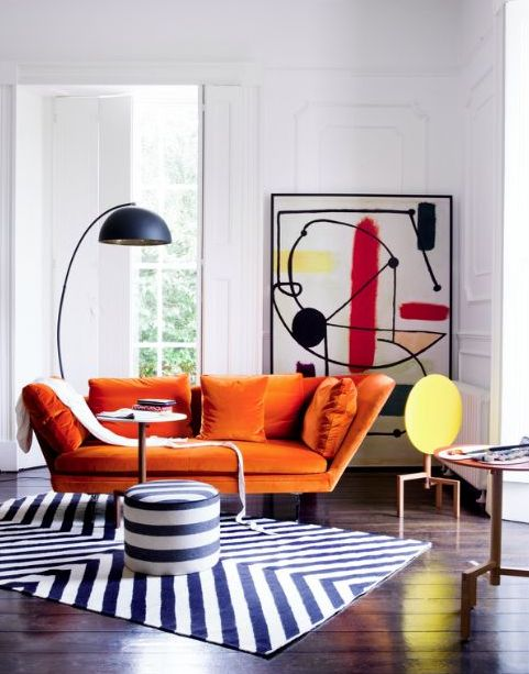 a whimsy living room with an orange loveseat, a bold abstract artwork, a floor lamp and a geometric rug and a pouf