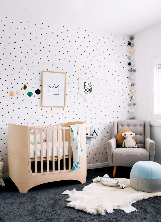 a whimsy modern nursery with a polka dot accent wall, a grey chair, a light stained crib, layered rugs and a color block pouf and cool lights