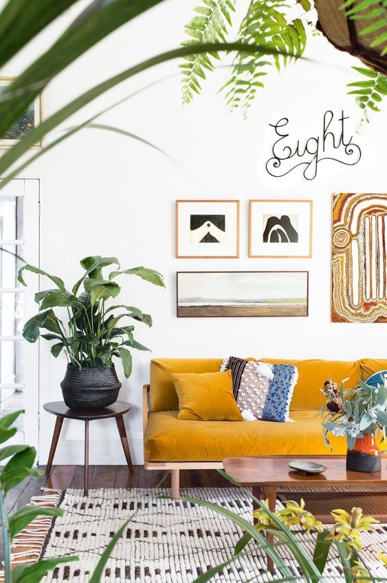 an airy and vivacious living room with a mustard sofa, a gallery wall, potted plants and a woven rug for a boho feel