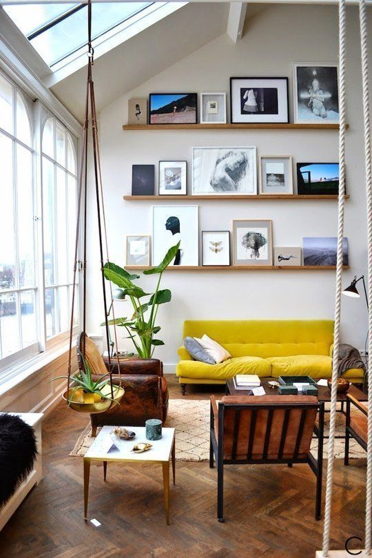 an airy living room with a ledge gallery wall going up to the ceiling, a yellow sofa, brown leather chairs and potted plants