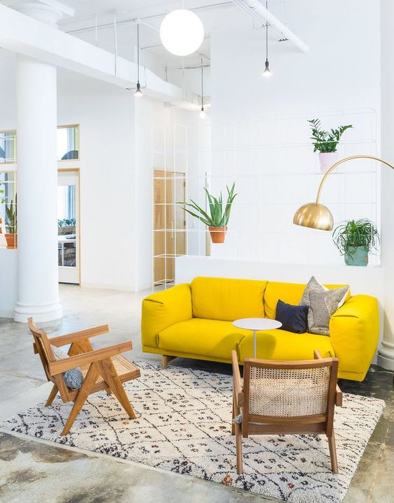 an airy living room with a neon yellow sofa, rattan chairs, a gold gallery wall and potted plants is amazing