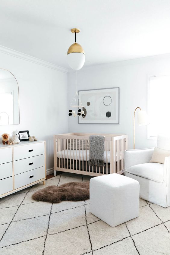 an airy modern nursery with white walls, white furniture and a light-stained crib, layered rugs and abstract decor