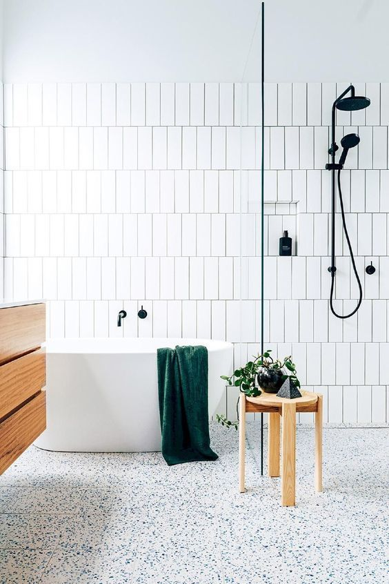 an airy neutral bathroom with white skinny tiles, a white terrazzo floor, a floating wooden vanity and a wooden stool