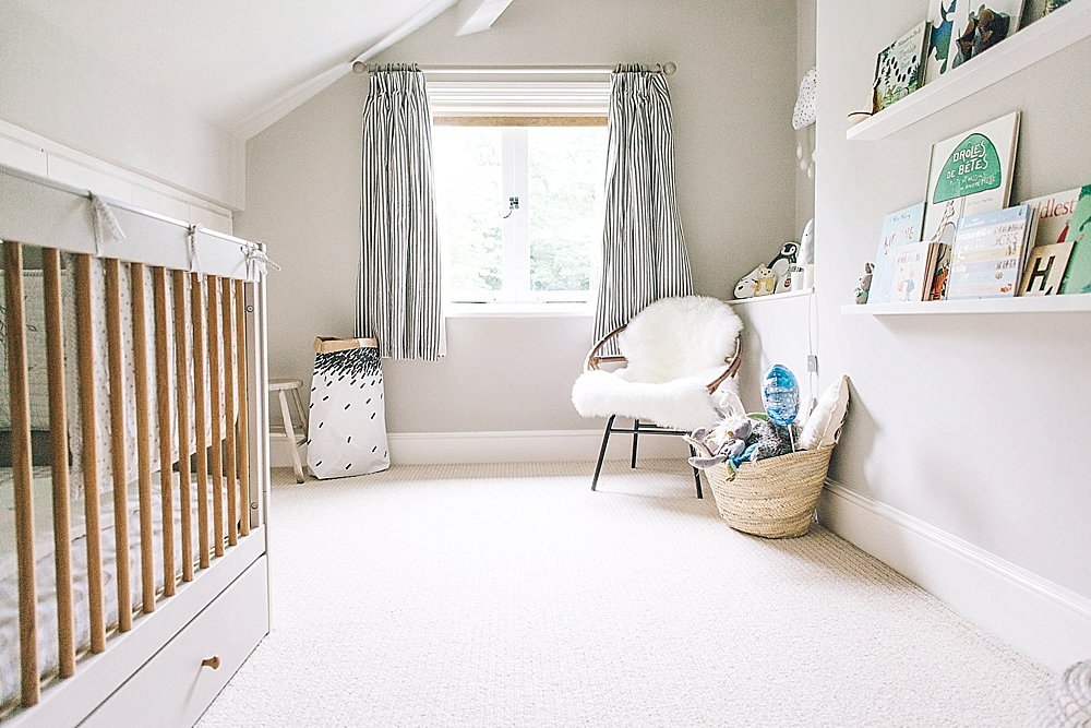 an airy neutral nursery with a grey crib, floating shelves, a rattan chair and a dresser plus striped curtains