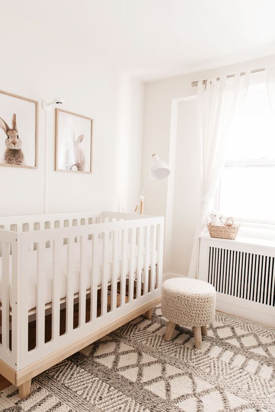 an airy neutral nursery with a white crib and a woven stool, a boho rug, a basket and a pretty and cute gallery wall