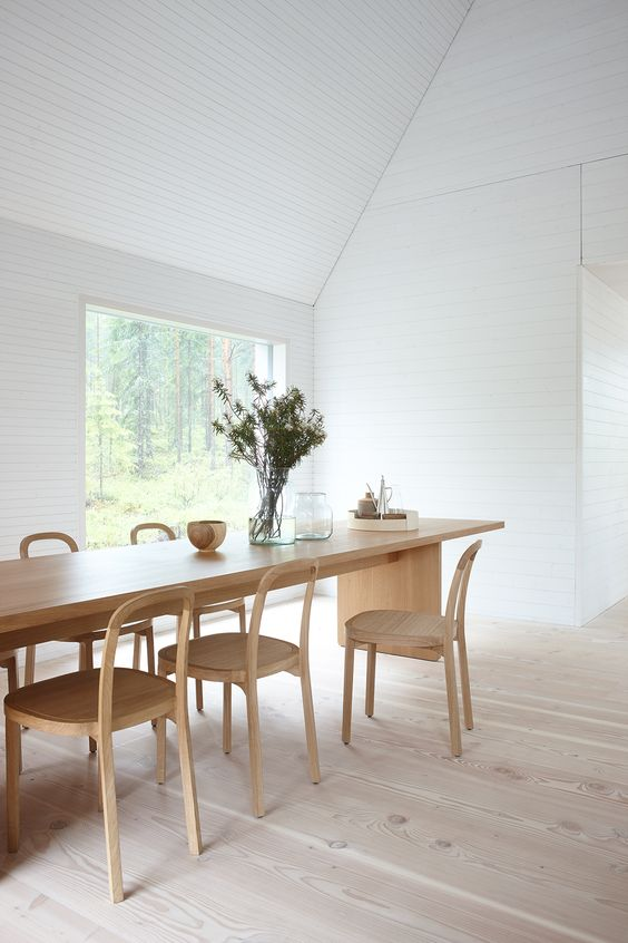 an airy white dining space with a view and a blonde wood dining set with chairs is a very welcoming and clean space