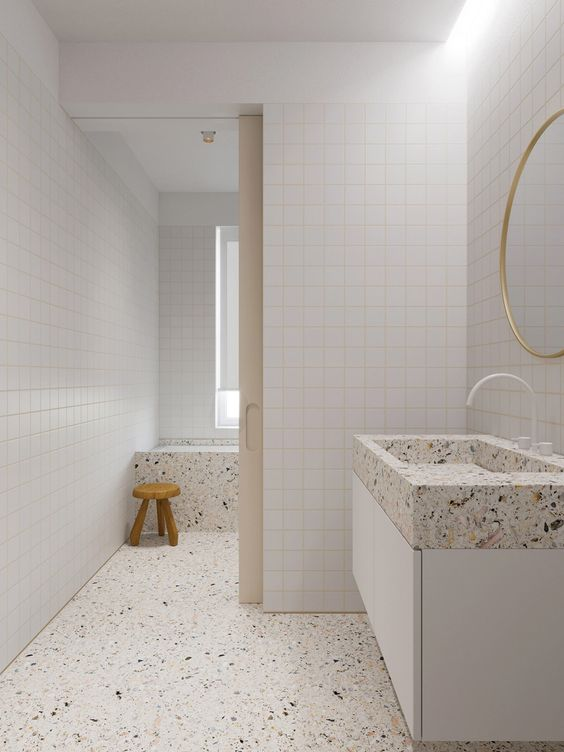 an all-neutral bathroom clad with white square tiles, and done with white terrazzo flooring and appliances is amazing