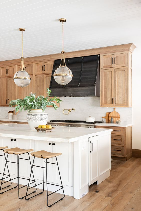 an amazing modern farmhouse kitchen with blonde wood cabinets, a white kitchen island, pendant lamps and blonde wood stools