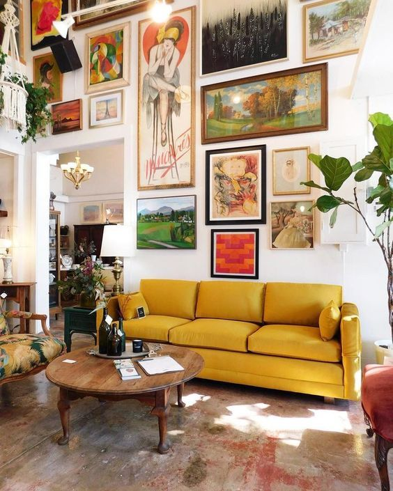 an artful living room with a bold gallery wall coming up to the ceiling, a yellow sofa, a vintage wooden table and a printed chair