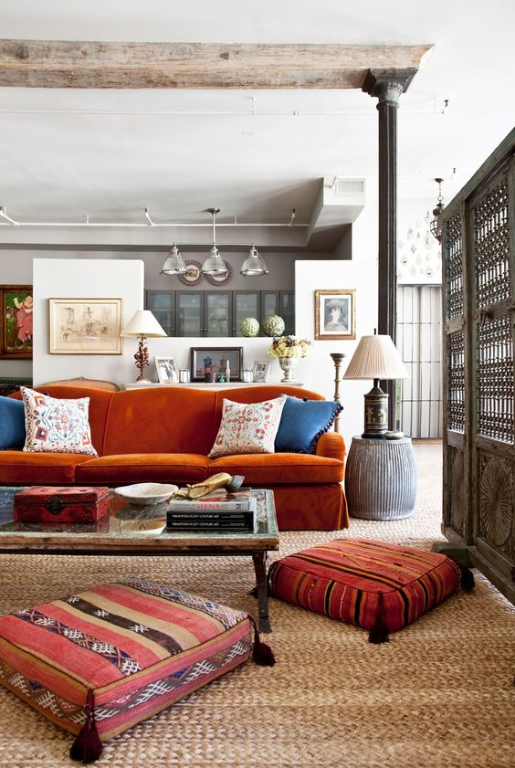 an eclectic living room with a burnt orange sofa, a low table and pretty tassel cushions and a table lamp