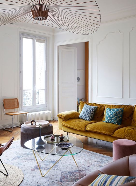 an exquisite Parisian living room with a mustard sofa, blush and brown chairs, a low glass table and a beautiful chandelier