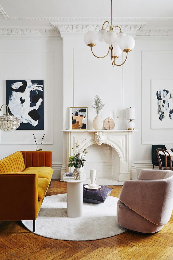 an exquisite Parisian living room with a non-working fireplace, a honey yellow sofa, a blush chair, a retro chandelier and lovely art