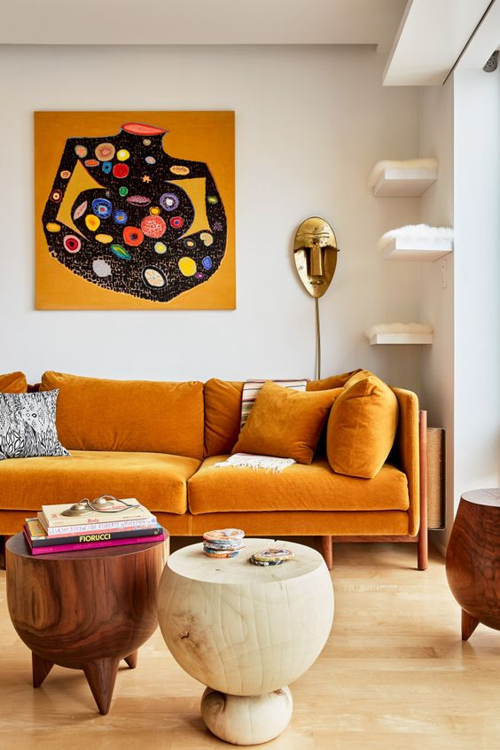 an exquisite living room with a honey yellow sofa, floating shelves for cats, round woodne tables and a bold artwork
