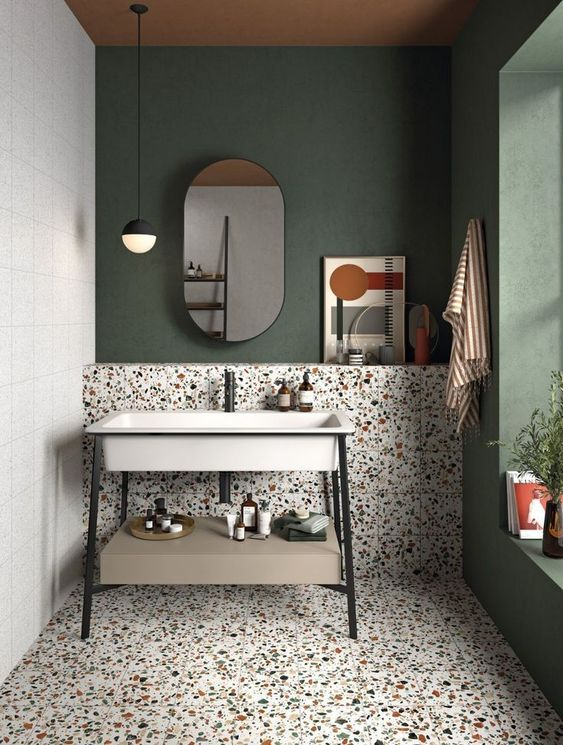 an eye catchy bathroom with a dark green accent wall, catchy terrazzo tiles on the floor and wall and a cool free standing sink