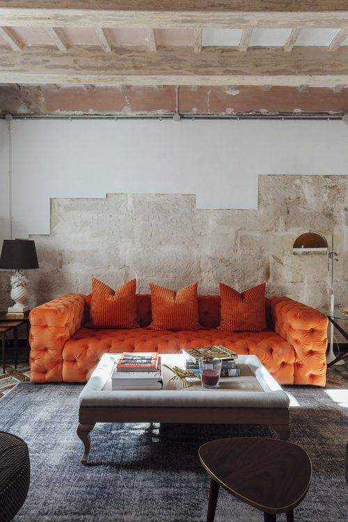 an industrial living room with rough walls, a refined orange tufted sofa, a low glass table and floor lamps