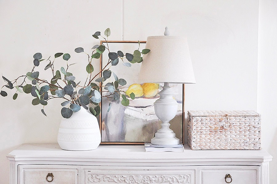 a lovely vintage inspired interior in white, with a whitewashed woven box that hides a router, which is a very stylish idea