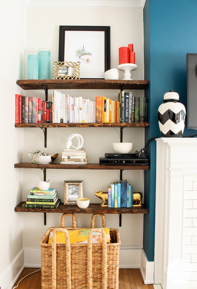 a router placed on a shelf makes part of decor like stacked books is a lovely idea to hide it right in the sight