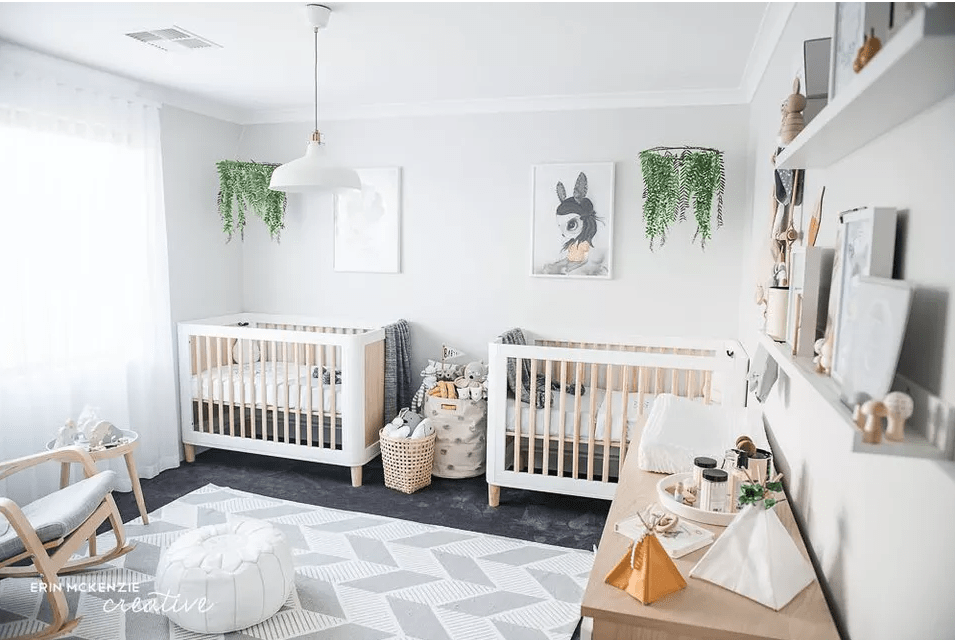 a beautiful and fresh twin nursery with white cribs and a chair, a round table and a stained dresser, greenery mobiles and pretty artworks