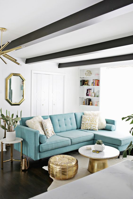 a beautiful mid-century modern living room with a fireplace, dark beams on the ceiling, a turquoise sofa and touches of gold for more elegance