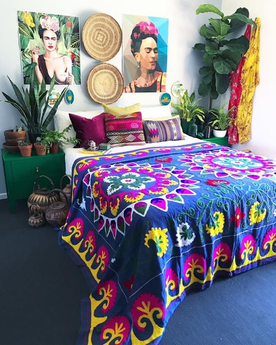 a boho maximalist bedroom with a navy carpet on the floor, emerald nightstands, a bold gallery wall, potted plants and bright textiles