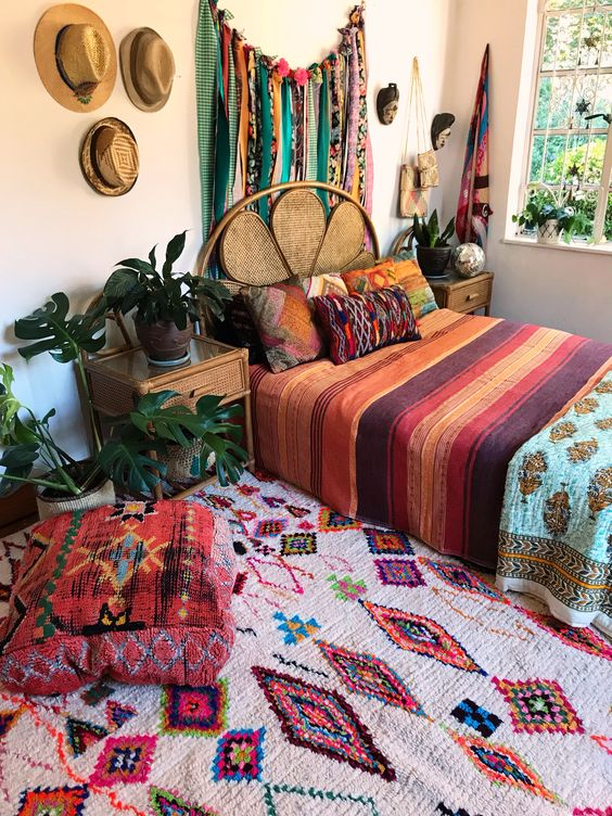 a boho maximalist bedroom with a rattan bed and wooden nightstands, a bold rug and bedding, a bunting and hats for decor on the wall