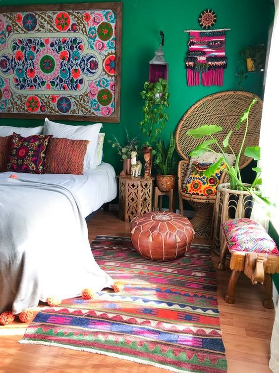 a boho maximalist bedroom with green walls, a colorful rug, a peacock chair, rattan and wooden furniture and a bold gallery wall