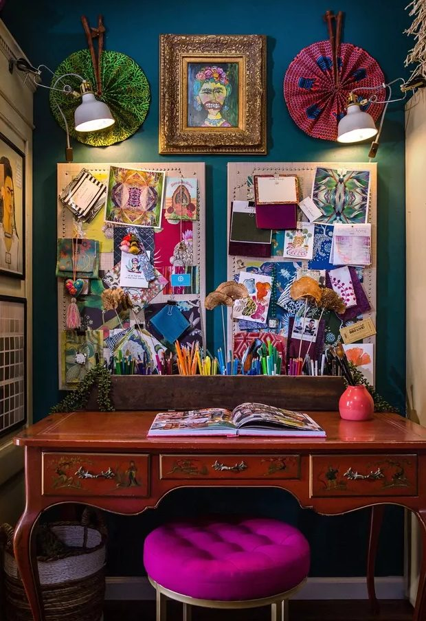 a boho maximalist home office with a navy accent wall, a vintage desk, a hot pink stool, a gallery wall and memo boards plus lights