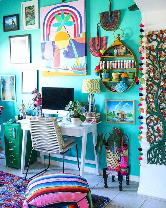 a boho maximalist home office with a turquoise accent wall, a white desk, a green cabinet and lots of artworks and textiles in bold shades