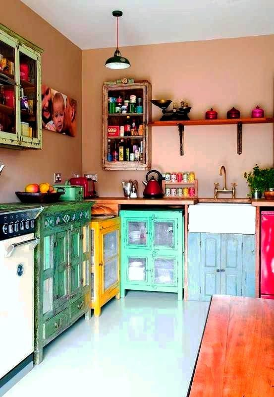 a boho maximalist kitchen with dusty pink walls, colorful mismatching cabinets and colorful cookware is amazing