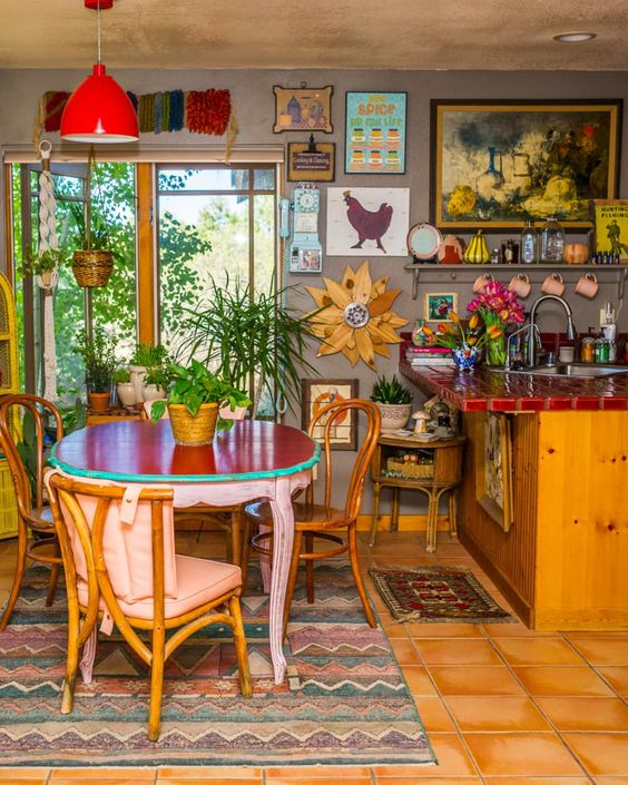 a boho maximalist kitchen with grey walls, light stained cabinets, a red tile countertop, a red table and mismatching chairs, lots of art and boho rugs