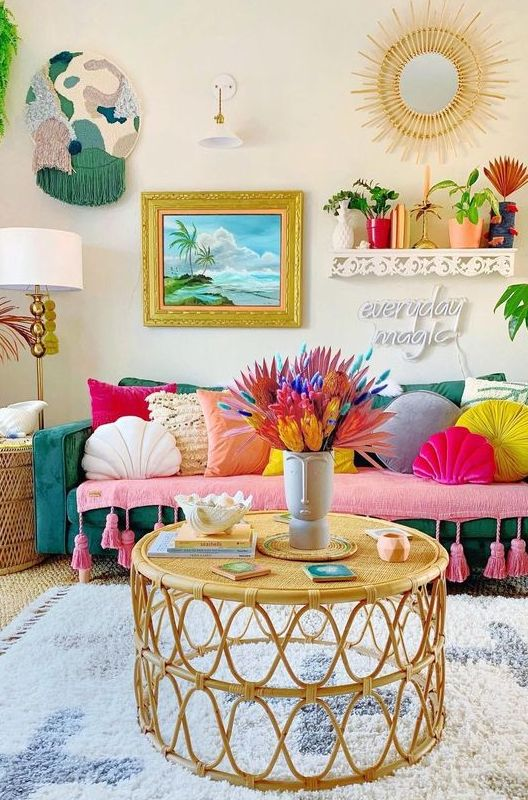 a boho maximalist living room with a green sofa, colorful pillows, rattan tables, bold artworks and a sunburst mirror and potted plants