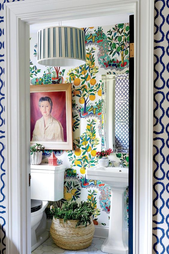a bold maximalist bathroom with fruit print wallpaper, a striped lamp, potted greenery, a bold artwork and vintage-inspired appliances