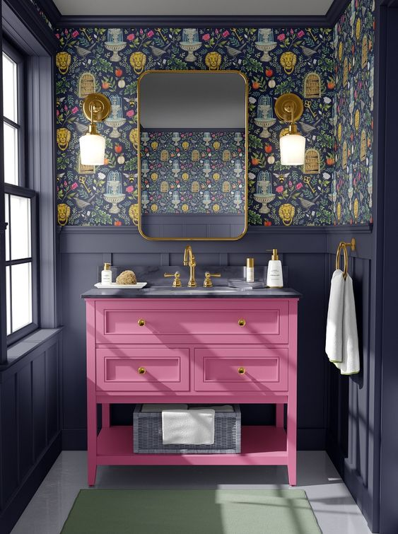 a bold maximalist bathroom with graphite grey paneling, dark floral wallpaper, a hot pink vanity and gold touches