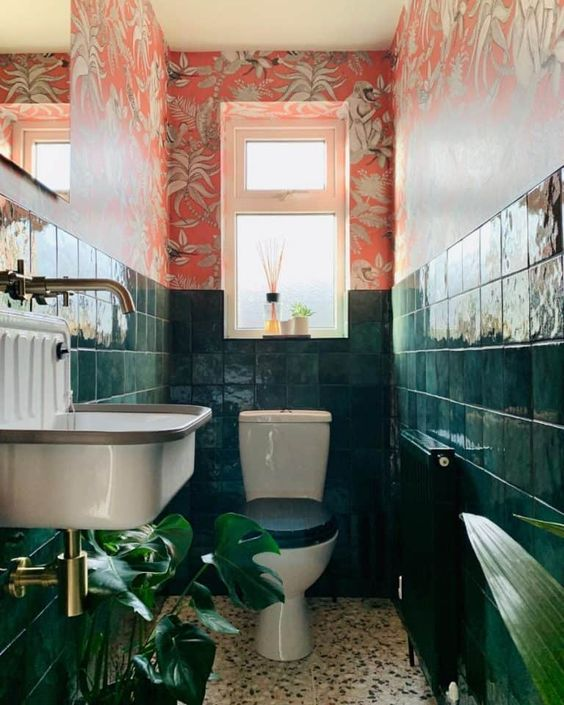 a bold maximalist bathroom with red floral wallpaper, dark green tiles, statement plants brass touches