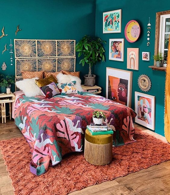 a bold maximalist bedroom with green walls, a bed with a woven headboard, colorful textiles and a bold gallery wall plus statement plants