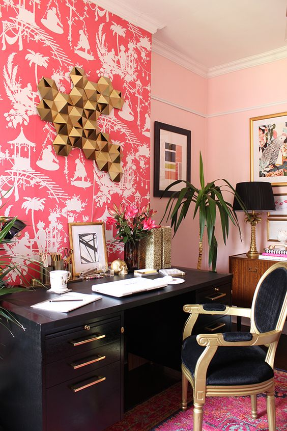 a bold maximalist home office with a bright pink wallpaper wall, a black desk, a refined black and gold chair, cool artworks on the walls