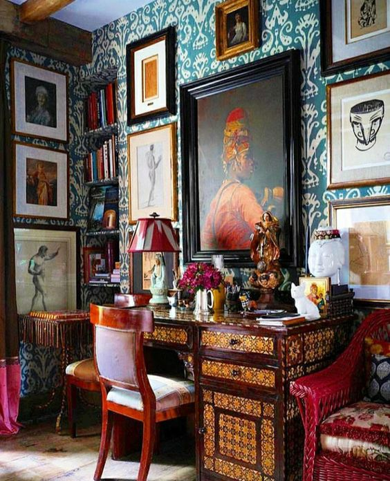 a bold maximalist home office with teal printed wallpaper, gallery wlal on several walls, an inlaid desk, bold printed chairs and a colorful lamp