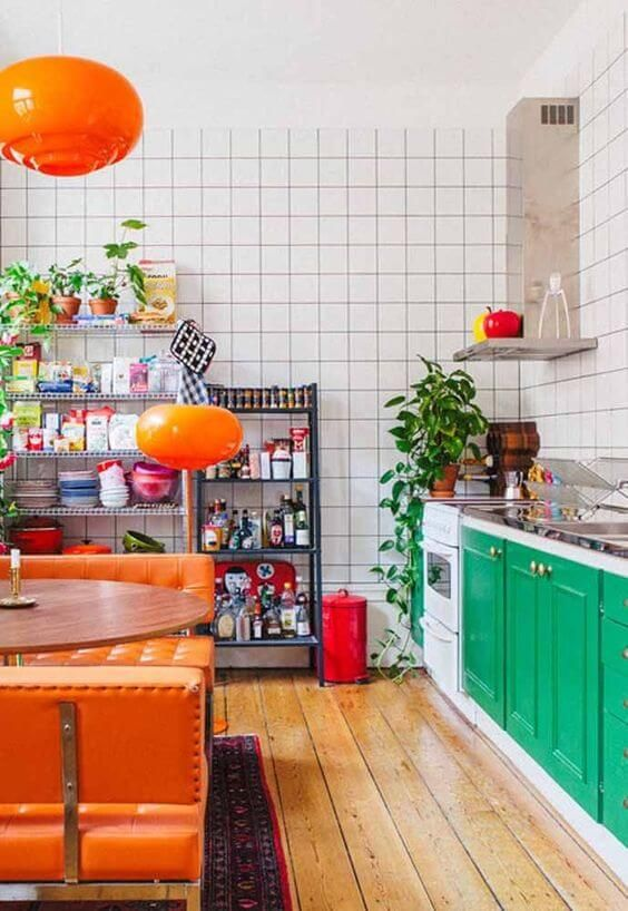 a bold maximalist kitchen with emerald cabinets, white tile walls, orange upholstered benches and lamps
