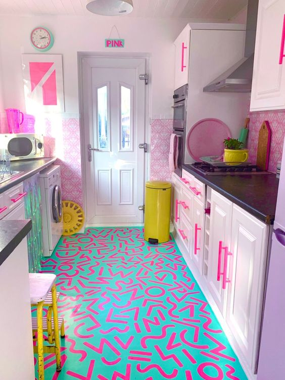 a bold maximalist kitchen with pink color block walls, lilac cabinets, a bold neon printed floor, neon yellow touches