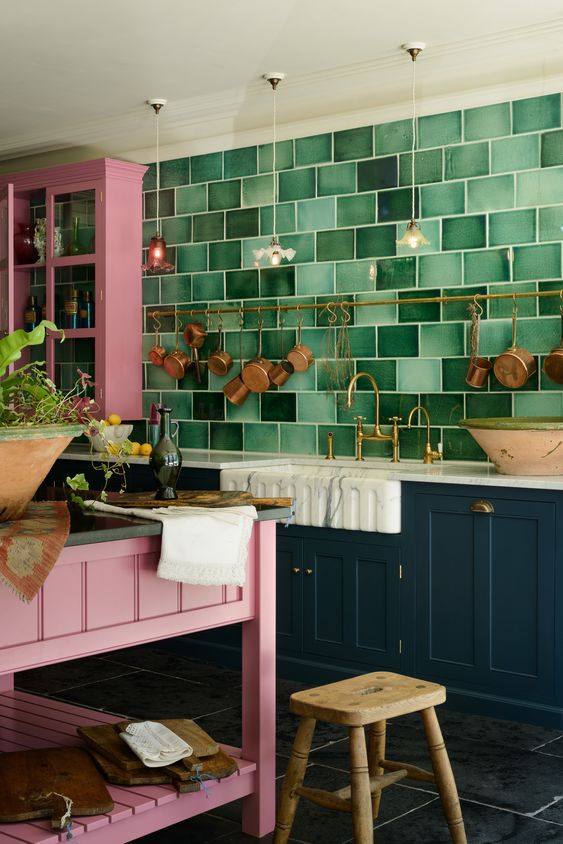 a bold maximalist kitchen with teal and pink cabinets, a green tile wall, a pink kitchen island and a wooden stool plus brass cookware