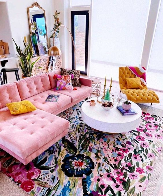 a bold maximalist living room with a colorful floral rug, a pink sofa, a yellow lounger and bright pillows and accessories