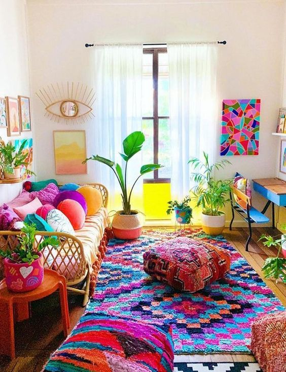 a bold maximalist living room with rattan and wooden furniture, colorful pillows, textiles and ottomans, potted plants