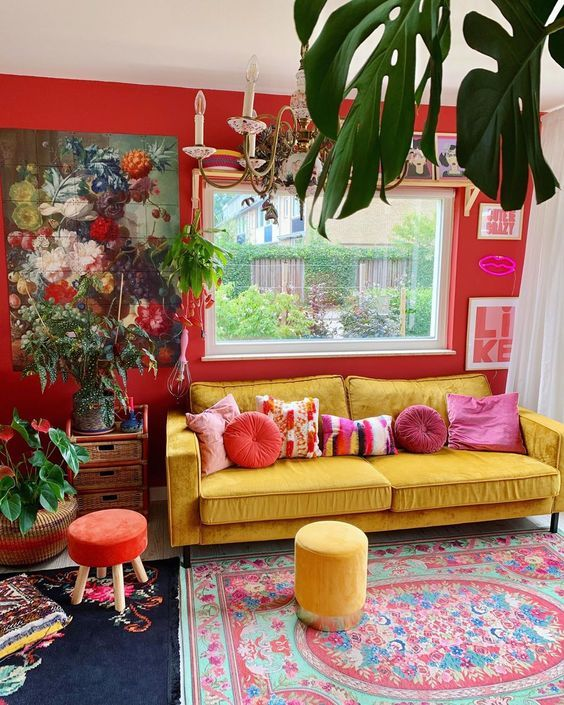a bold maximalist living room with red walls, a yellow sofa and colorful stools, bold rugs, lovely artworks and potted plants