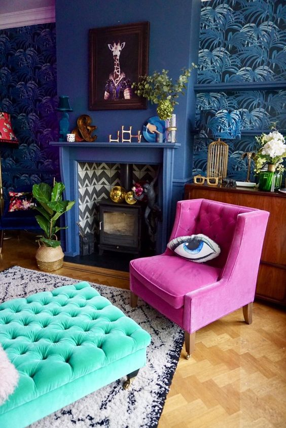 a bold maximalist living room with tropical leaf wallpaper, a blue fireplace, a fuchsia chair and a turquoise ottoman, bold art and decor
