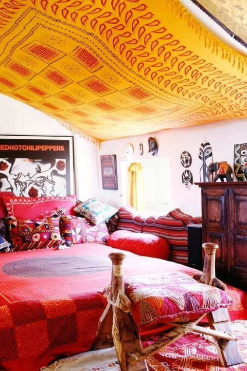 a bold maximalist space with pink walls, a wooden furniture, colorful bedding and pillows, a yellow canopy over the space