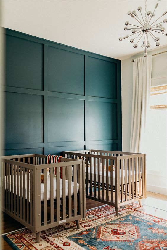 a bold twin nursery with a navy paneled wall, neutral cribs, a disco ball chandelier and a bright printed rug