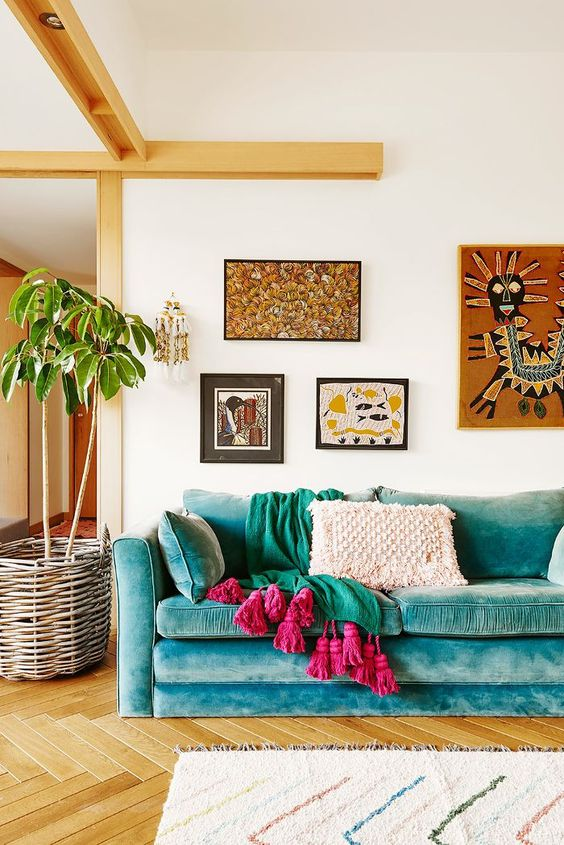 a bright boho living room with a turquoise sofa, bright textiles, a bright boho gallery wlal and a potted plant in a basket