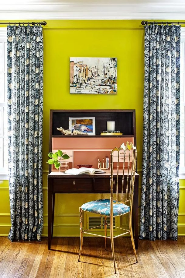 a bright home office with neon yellow walls, a vintage dark stained desk, a gilded chair with a tropical seat and printed curtains